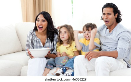 Cute siblings watching TV with their parents in the living room