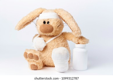 Cute sick bandaged hare with a jar of medicines on a white background.