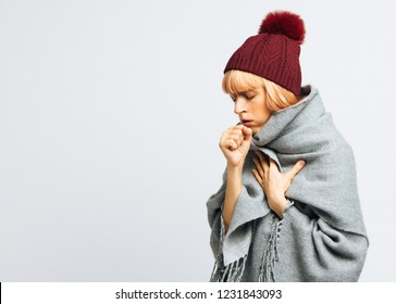 Cute sick young teen woman in red hat, wrapped in warm scarf coughing, closed eyes.Female feeling the first symptoms of illness, isolated.Bronchitis, cold, sickness concept.Fit of coughing. Flu season