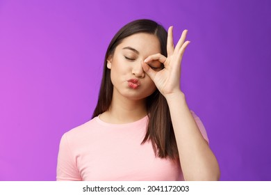 Cute silly asian female brunette folding lips kiss lovely expression, close eyes dreamy send muah, show perfection, okay ok sign, stand purple background carefree and cheerful