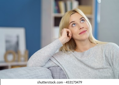 Cute single daydreaming woman in gray sweatshirt with hand on side of head looking upward while grinning on sofa in living room