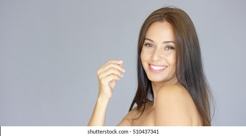 Cute single young adult woman with hand near face