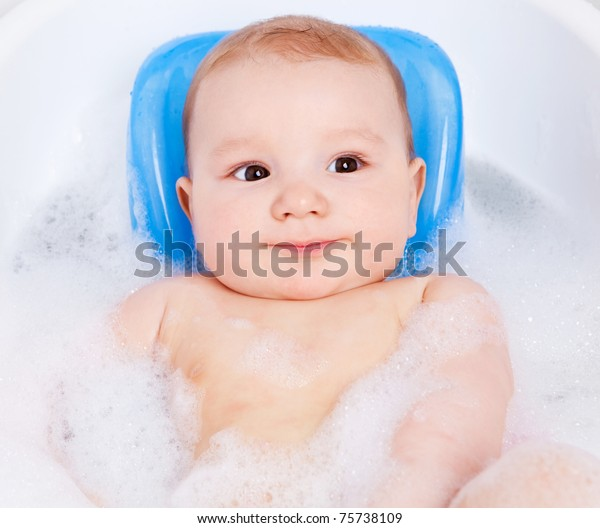 cute six months old baby taking a relaxing bath with foam