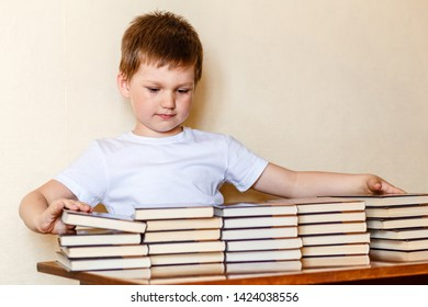 a cute six-year-old boy sits at a Desk and puts books on stacks. first-grader