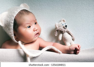 Cute sleeping baby, newborn and mothercare concept. Infant baby asian boy sleeping with teddy bear toy under white blanket