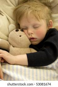 Cute sleeping child cuddling teddy bear