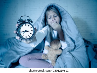 Cute sleepless little girl sitting on bed showing alarm clock looking tired having sleeping troubles staying asleep at night or waking too early in Children Insomnia Anxiety and Sleep Disorders.