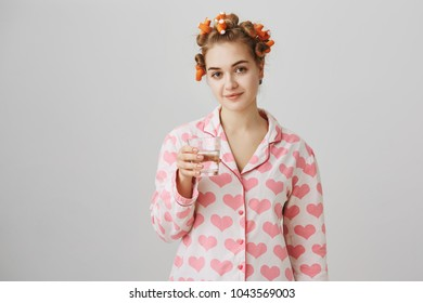 Cute sleepy european woman wearing hair rollers smiling at camera while standing with glass of water in pyjamas with printed hearts, looking in mirror before going to bed over gray background.