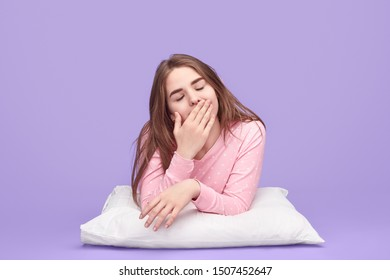 Cute sleepy teenager in sleepwear closing eyes and covering mouth while lying on pillow and yawning during bedtime against purple background