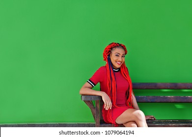 Cute and slim african american girl in red dress with dreadlocks posed on bench background green wall. Stylish black model.