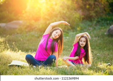 Cute smal daughter and mother do exerciese, fitness, yoga in morning park