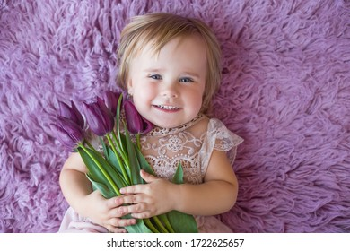 cute small baby in nice dress possing and smiling laying with tulips on flokati background