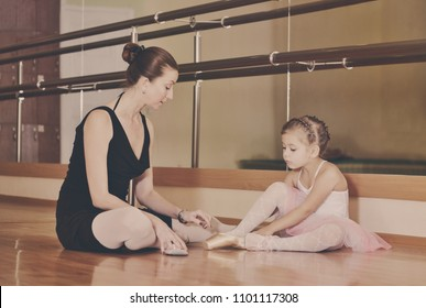 Cute small ballerina sitting on floor with her coach.