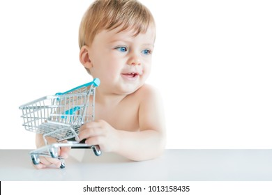 Cute small blue-eyed blond boy holding a toy shopping cart at the table on a white background