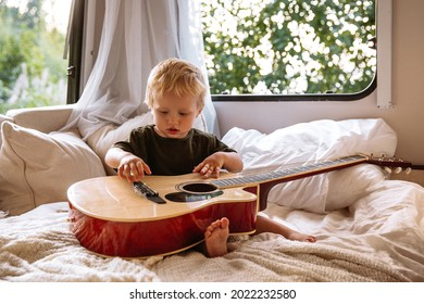 Cute small boy of 2 trying to play guitar sitting alone on bed in trailer rv. Adorable little child entertain hold musical instrument travelling with parents on camper. Childhood and love concept