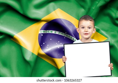 Cute small boy holding emtpy sign in front of flag of Brazil