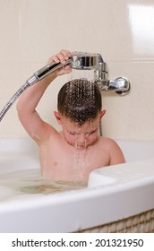 Cute small boy showering in the bath holding the flexible shower nozzle over his head as he washes his hair in the spray