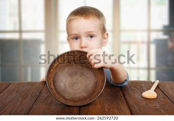 Le petit garçon mignon assis sur une table en bois montre une plaque vide