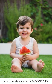 Cute small child holding a piece of watermelon sitting on a grass. Vertical outdoors shot.