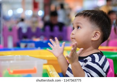 cute small child sitting and clapping hands in kid playground