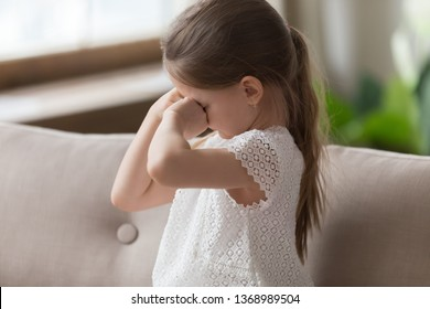 Cute small daughter sitting on sofa cover face with hands feels offended upset or lonely crying wiping tears. Naughty kid manipulate their parents, bad manners, behaviour problem or punishment concept