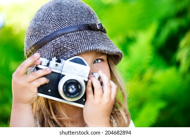 Cute small girl with the camera try to make a shot