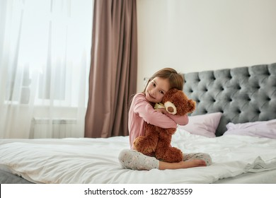 A cute small girl smiling embracing a teddybear while sitting barefoot on a huge bed wearing pyjamas in a bright spacy bedroom at home