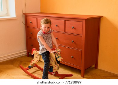 Cute small girl swings on rocking horse. Small girl wears  red glasses. Little girl plays in living room