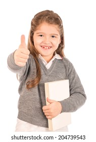 A cute small girl wearing a school uniform giving a thumbs up while holding a blank book. Isolated on white.