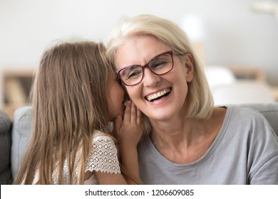 Cute small granddaughter whisper something in granny ear, grandmother and grandchild share secrets having sincere talk at home, grandma and little girl have fun at home together laughing