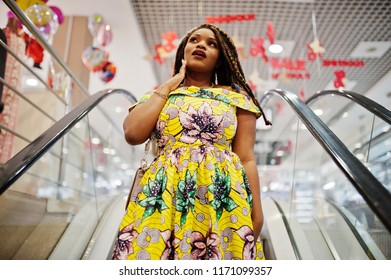 Cute small height african american girl with dreadlocks, wear at coloured yellow dress, standing at escalator on shopping center. Surprised face.