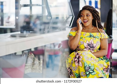 Cute small height african american girl with dreadlocks, wear at coloured yellow dress, sitting on cafe at shopping center and speaking on phone.