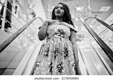 Cute small height african american girl with dreadlocks, wear at coloured yellow dress, standing at escalator on shopping center. Surprised face. Black and white.