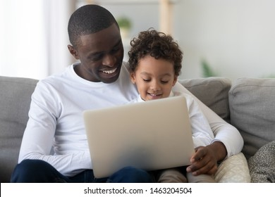 Cute small kid son learning using laptop watching cartoons with happy black dad, african american mixed race family father teaching child having fun with computer device sit together on couch at home