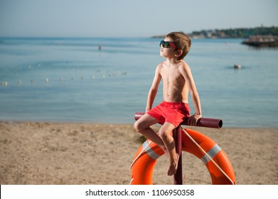 cute small kid in sunglasses sitting on beach with lifebuoy outdoor summer like baywatch movie heroes