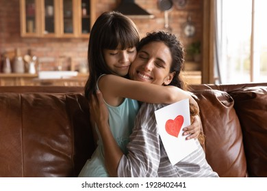 Cute small Latino 8s girl child hug happy young mother congratulate with birthday give handmade postcard. Loving little daughter embrace Hispanic mom greeting with woman day present gift card.
