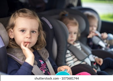 cute small sisters in gray car seats in the car