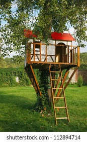 Cute small tree house for kids on backyard. German style.