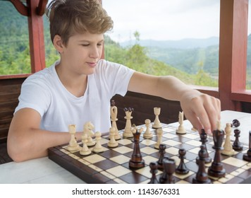 cute, smart, handsome boy in white tshirt  plays chess  in the summer arbor with mountain background. Education concept, intellectual game. Chess lesson, training concept