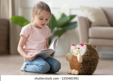 Cute smart little kid girl playing alone reading story to fluffy hedgehog sitting on warm floor at home, funny creative preschool small child holding book teaching toy, children imagination education