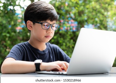 A cute and smart looking student boy sitting outdoor in the campus using computer laptop to coding and study in his project. Teen self esteem, problem solving skills, 21st century education concept.