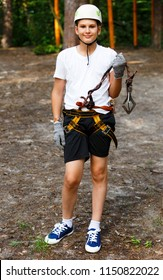 cute, smart, young, sporty boy in white tshirt and helmet spends his free time in the adventure rope park in the summer. hobby, active lifestyle concept