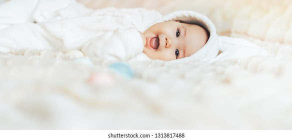 Cute smile happy little baby, playing with colorful easter eggs lying on bed in white rabbit hare costume look at camera