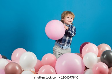 Cute smile from little boy holding big, pink ballon on blue background. Little child is going to throw somebody his ballon. Color background contrast between blue background and pink ballons