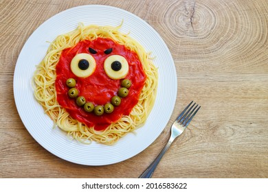 Cute smile monster spaghetti creative food for Halloween made from spaghetti,tomato sauce,black olive,mozzarella sheet and green olives on plate with wooden table background.Art food idea for kids