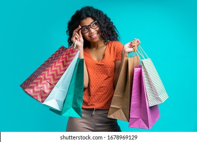 Cute smiling african american girl in casual outfit and trendy spectacles posing with piles of paper shopping bags isolated over blue background.
