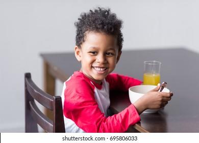 cute smiling african-american kid eating healthy breakfast
