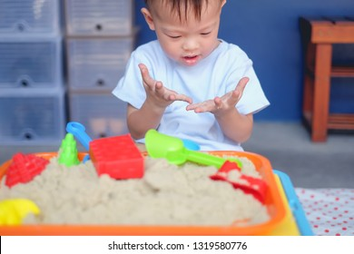 Cute smiling Asian 2 - 3 years old toddler boy playing with kinetic sand in sandbox at home / nursery / day care, Fine motor skills development, Montessori education, Creative play for kids concept
