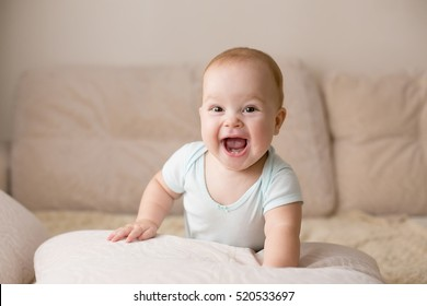 Cute smiling baby in blue bodysuit on a beige couch.