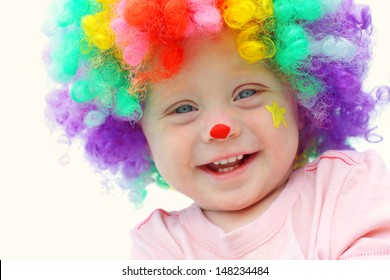 A cute, smiling baby boy is dressed up in a clown costume with colorful wig and clown make up face paint